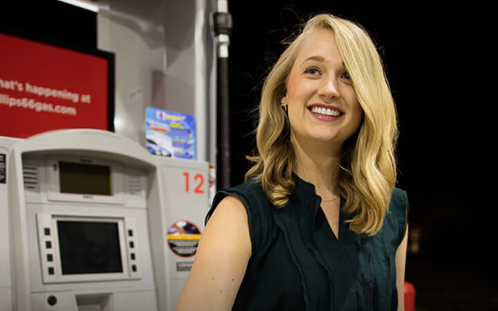Young female smiling while pumping gas at a Phillips 66 gas station